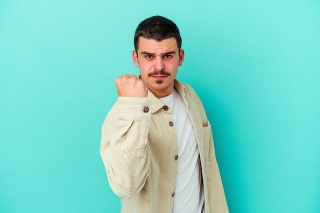 Młody kaukaski mężczyzna na białym tle na niebieskiej ścianie pokazano pięść, agresywny wyraz twarzy.