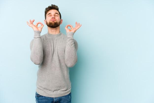 Młody kaukaski mężczyzna na białym tle na niebieskiej ścianie relaksuje się po ciężkim dniu pracy, wykonuje jogę.