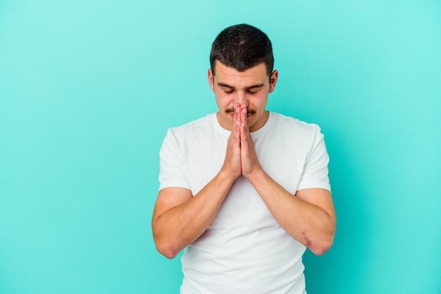 Młody kaukaski mężczyzna na białym tle na niebieskiej ścianie, trzymając się za ręce w modlitwie blisko ust, czuje się pewnie