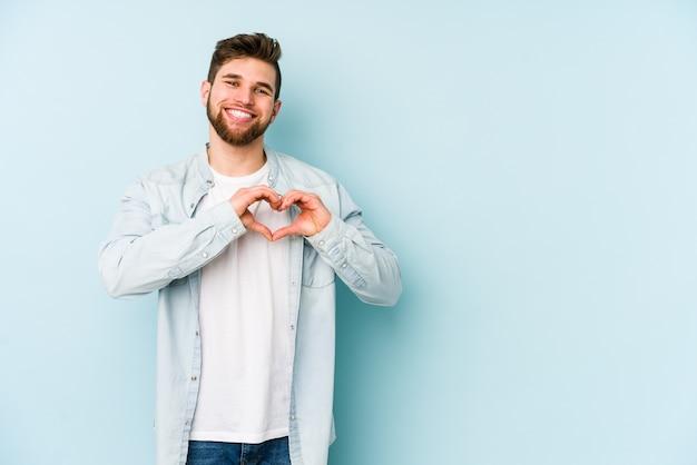 Młody kaukaski mężczyzna na białym tle na niebieskiej ścianie, uśmiechając się i pokazując kształt serca rękami.