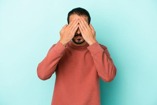 Młody kaukaski mężczyzna na białym tle na niebieskim tle boi się zasłaniając oczy rękami.