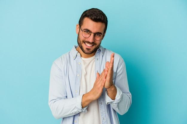 Młody kaukaski mężczyzna na białym tle na niebieskim tle czuje się energiczny i wygodny, pocierając ręce pewnie.