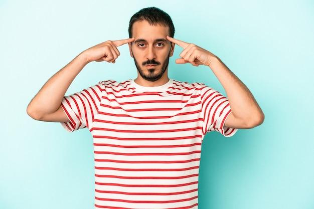 Młody kaukaski mężczyzna na białym tle na niebieskim tle koncentruje się na zadaniu, trzymając palce wskazujące wskazujące głowę.