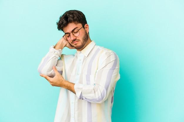 Młody kaukaski mężczyzna na białym tle na niebieskim tle masuje łokieć, cierpi po złym ruchu.