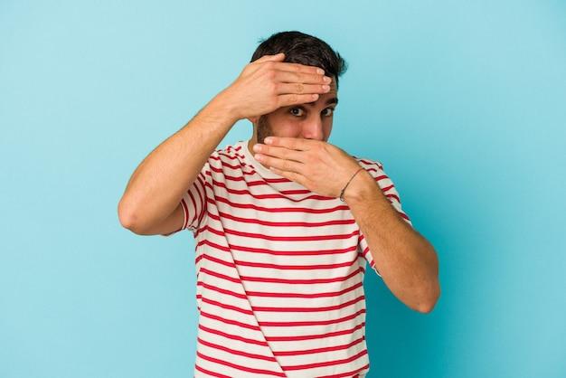 Młody kaukaski mężczyzna na białym tle na niebieskim tle mruga do kamery palcami, zawstydzony zakrywający twarz.
