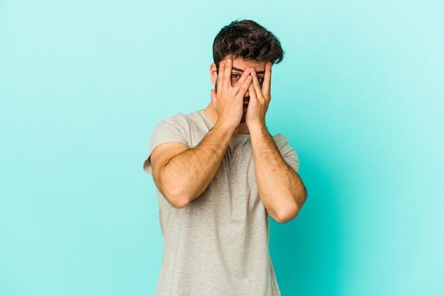 Młody kaukaski mężczyzna na białym tle na niebieskim tle mrugać do kamery palcami, zakłopotany zasłaniając twarz.