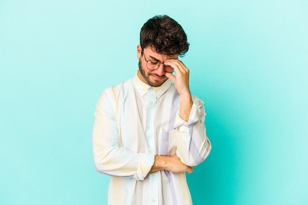 Młody kaukaski mężczyzna na białym tle na niebieskim tle o ból głowy, dotykając przodu twarzy.