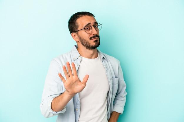 Młody kaukaski mężczyzna na białym tle na niebieskim tle odrzucając kogoś pokazując gest obrzydzenia.