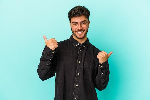Młody kaukaski mężczyzna na białym tle na niebieskim tle podnosząc kciuki do góry, uśmiechnięty i pewny siebie.