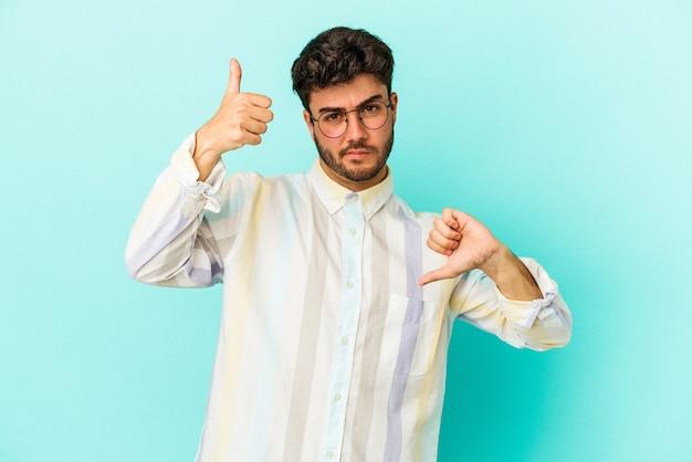 Młody kaukaski mężczyzna na białym tle na niebieskim tle pokazując kciuk w górę i kciuk w dół, trudny wybór koncepcji