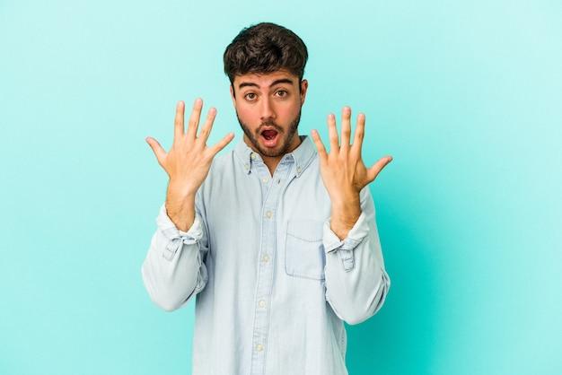 Młody kaukaski mężczyzna na białym tle na niebieskim tle pokazuje numer dziesięć z rąk.