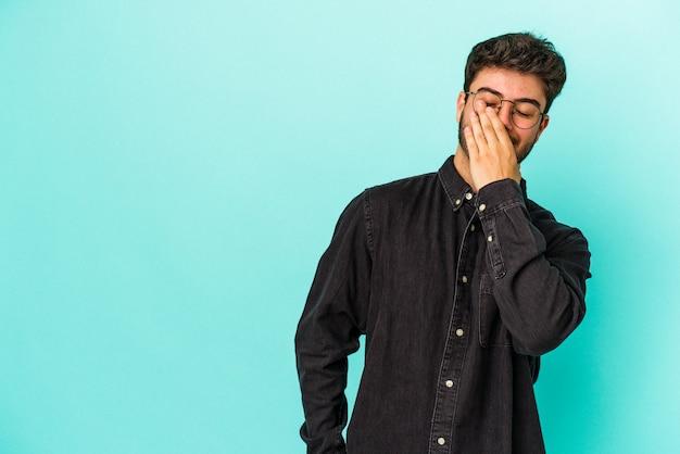 Młody kaukaski mężczyzna na białym tle na niebieskim tle śmiejąc się szczęśliwy, beztroski, naturalne emocje.
