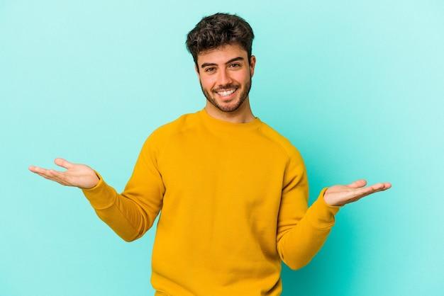 Młody kaukaski mężczyzna na białym tle na niebieskim tle sprawia, że skala z rękami, czuje się szczęśliwy i pewny siebie.