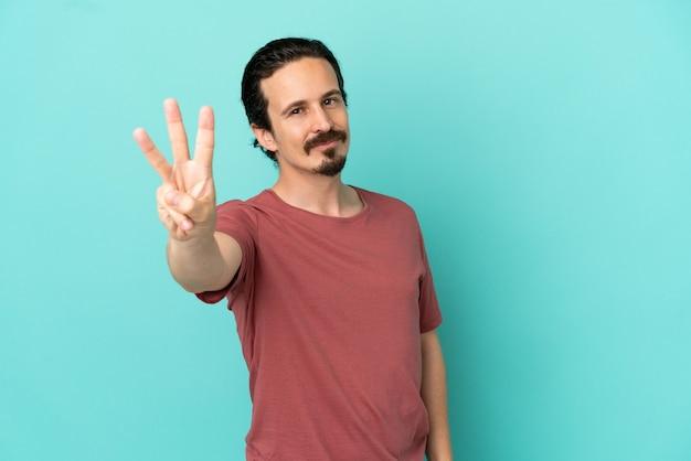 Młody kaukaski mężczyzna na białym tle na niebieskim tle szczęśliwy i liczący trzy palcami