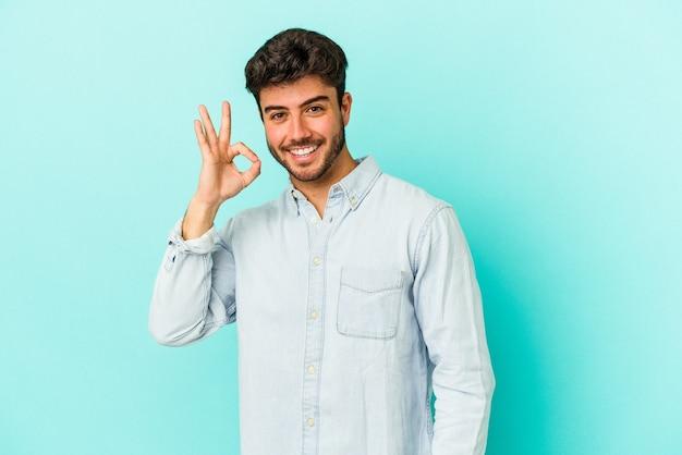 Młody kaukaski mężczyzna na białym tle na niebieskim tle wesoły i pewny siebie, pokazując ok gest.
