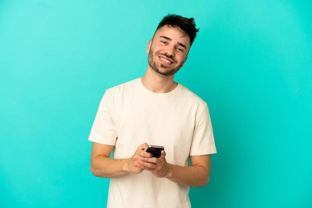 Młody kaukaski mężczyzna na białym tle na niebieskim tle wysyła wiadomość za pomocą telefonu komórkowego