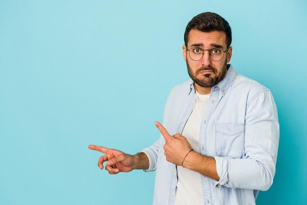 Młody kaukaski mężczyzna na białym tle na niebieskim tle zszokowany, wskazując palcami wskazującymi na miejsce.