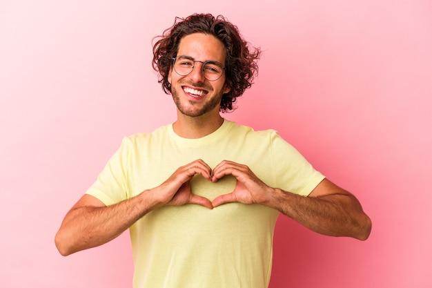 Młody kaukaski mężczyzna na białym tle na różowym bakcground uśmiechnięty i pokazujący kształt serca rękami.