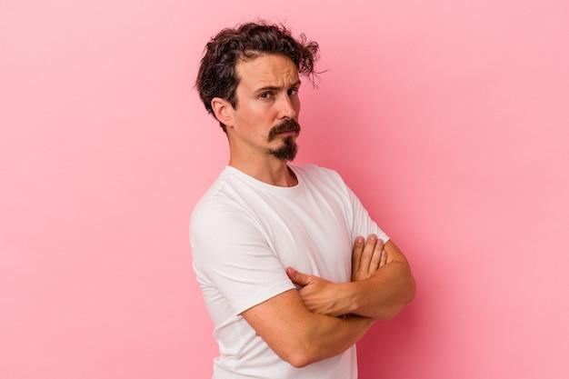 Młody kaukaski mężczyzna na białym tle na różowym tle podejrzany, niepewny, badający ciebie.