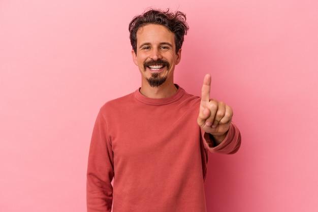 Młody kaukaski mężczyzna na białym tle na różowym tle pokazując numer jeden palcem.