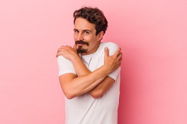 Młody kaukaski mężczyzna na białym tle na różowym tle przytula się, uśmiechając się beztrosko i szczęśliwy.