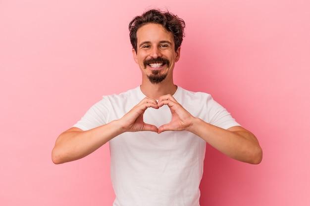 Młody kaukaski mężczyzna na białym tle na różowym tle, uśmiechając się i pokazując kształt serca rękami.