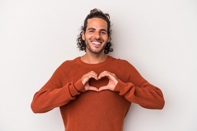 Młody kaukaski mężczyzna na białym tle na szarym tle, uśmiechając się i pokazując kształt serca rękami.