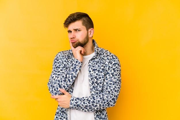 Młody kaukaski mężczyzna na białym tle na żółtej przestrzeni niezadowolony patrząc w kamerę z sarkastycznym wyrazem.