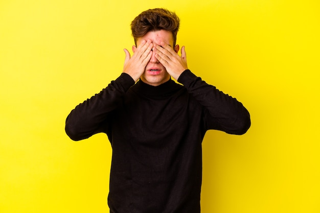 Młody kaukaski mężczyzna na białym tle na żółtej ścianie boi się zakrywających oczy rękami.