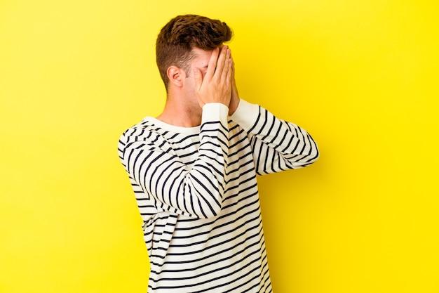 Młody kaukaski mężczyzna na białym tle na żółtej ścianie boi się zakrywających oczy rękami