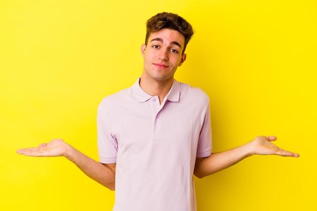 Młody kaukaski mężczyzna na białym tle na żółtej ścianie przedstawiający mile widziane wyrażenie.