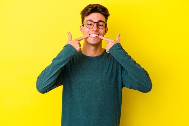 Młody kaukaski mężczyzna na białym tle na żółtej ścianie uśmiecha się, wskazując palcami na usta.