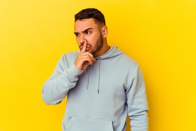 Młody kaukaski mężczyzna na białym tle na żółtym tle dochowując tajemnicy lub prosząc o ciszę.