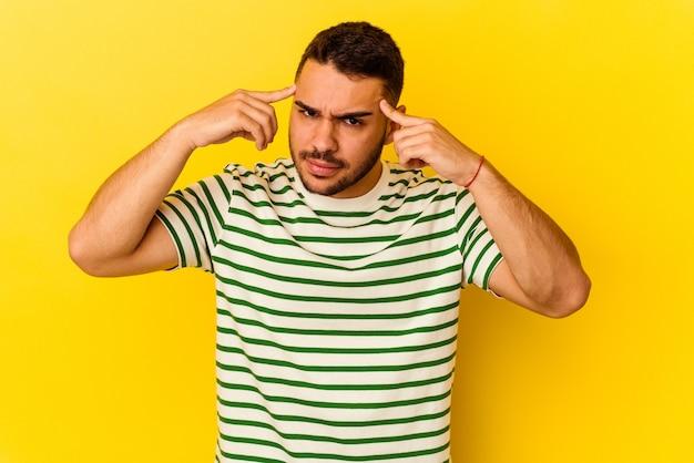 Młody kaukaski mężczyzna na białym tle na żółtym tle koncentruje się na zadaniu, trzymając palce wskazujące wskazujące głowę.
