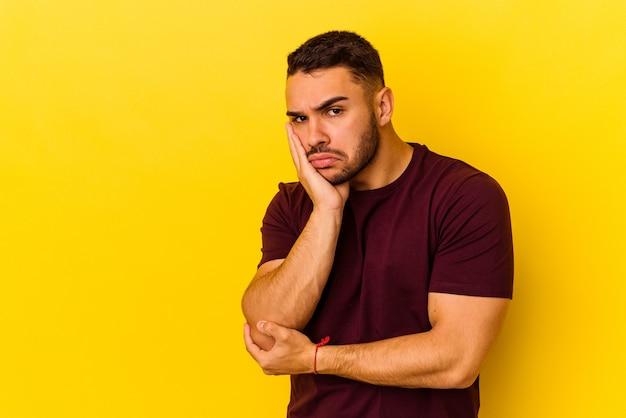 Młody kaukaski mężczyzna na białym tle na żółtym tle, który czuje się smutny i zamyślony, patrząc na miejsce.