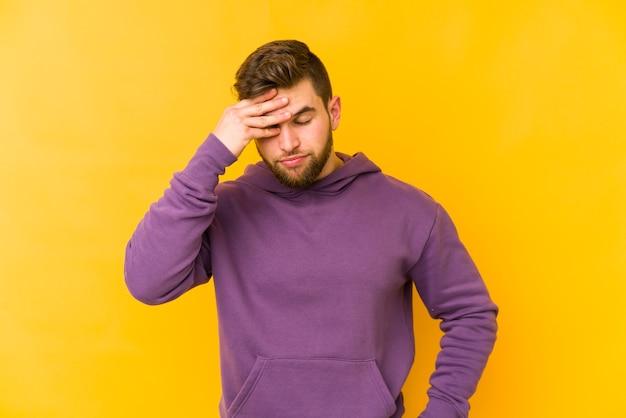 Młody kaukaski mężczyzna na białym tle na żółtym tle o bólu głowy, dotykając przedniej części twarzy.