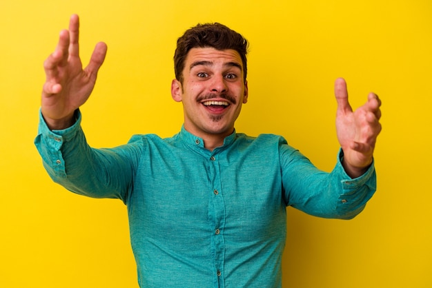 Młody kaukaski mężczyzna na białym tle na żółtym tle otrzymujący miłą niespodziankę, podekscytowany i podnoszący ręce.