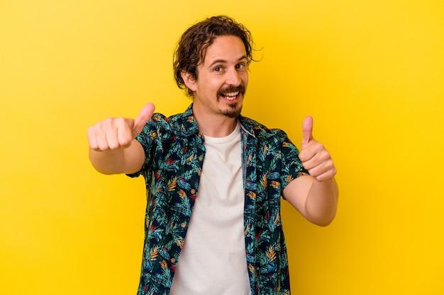 Młody kaukaski mężczyzna na białym tle na żółtym tle, podnosząc oba kciuki do góry, uśmiechnięty i pewny siebie.