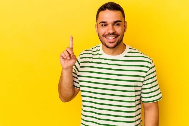 Młody kaukaski mężczyzna na białym tle na żółtym tle pokazując numer jeden palcem.
