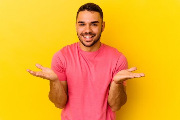 Młody kaukaski mężczyzna na białym tle na żółtym tle sprawia, że skala z rękami, czuje się szczęśliwy i pewny siebie.