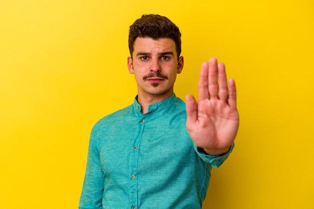 Młody kaukaski mężczyzna na białym tle na żółtym tle stojący z wyciągniętą ręką pokazując znak stop, uniemożliwiając.
