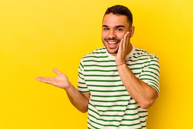Młody kaukaski mężczyzna na białym tle na żółtym tle trzyma miejsce na dłoni, trzymaj rękę nad policzkiem. zdumiony i zachwycony.
