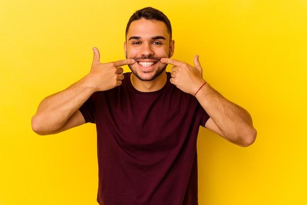 Młody kaukaski mężczyzna na białym tle na żółtym tle uśmiecha się, wskazując palcami na usta.