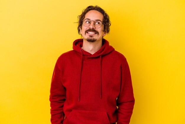 Młody kaukaski mężczyzna na białym tle na żółtym tle zrelaksowany i szczęśliwy śmiejąc się, szyja rozciągnięta pokazując zęby.