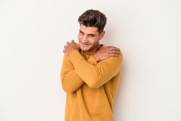Młody kaukaski mężczyzna na białym tle przytula się, uśmiechając się beztrosko i szczęśliwie.