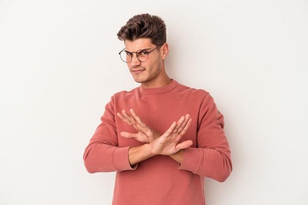 Młody kaukaski mężczyzna na białym tle robi gest odmowy
