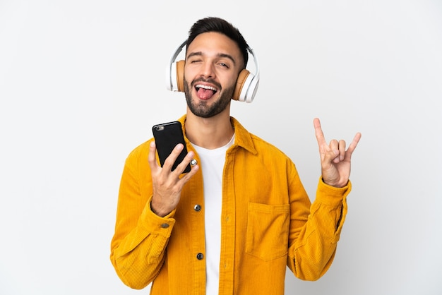 Młody kaukaski mężczyzna na białym tle słuchający muzyki za pomocą telefonu komórkowego wykonującego rockowy gest