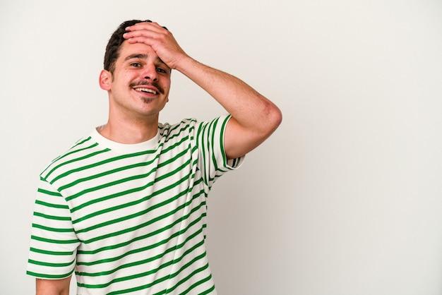 Młody kaukaski mężczyzna na białym tle śmiejąc się szczęśliwy, beztroski, naturalne emocje.