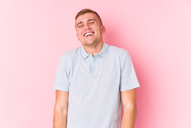 Młody kaukaski mężczyzna na białym tle śmieje się i zamyka oczy, czuje się zrelaksowany i szczęśliwy.
