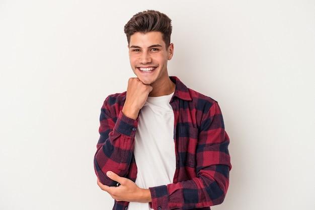 Młody kaukaski mężczyzna na białym tle uśmiechnięty szczęśliwy i pewny siebie, dotykając podbródka ręką.